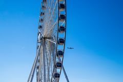 Airplane flies past a ferris wheel in a clear blue sky in spring. With open copy space stock photos