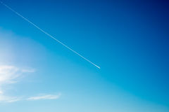 Airplane flies in white clouds in a blue sky and leaving trail Royalty Free Stock Images