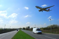 Airplane in flight. Above busy road near to Heathrow airport Royalty Free Stock Image