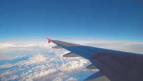 Airplane flight. Wing of an airplane flying above the clouds. View from the window of the plane. Aircraft. Traveling by stock footage