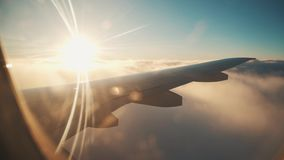 Airplane flight. Wing of an airplane flying above the clouds with sunset sky. stock footage