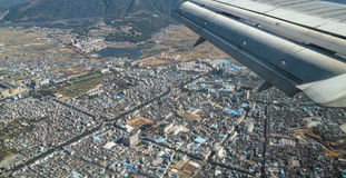 Airplane fly over a city. Yunnan of China Stock Photo