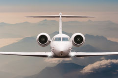Airplane fly over clouds and Alps mountain on sunset. Front view of a big passenger or cargo aircraft, business jet Royalty Free Stock Photo