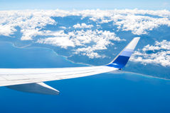 Airplane fly over land and ocean Royalty Free Stock Photos