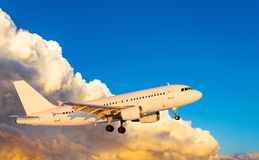 Airplane at fly on the sky with clouds sunset.  Royalty Free Stock Photography
