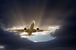 The airplane fly in to gray clouds Stock Photos
