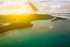 Airplane flying above beach blue sea island, taken from window w. Ith wing and, light filter, Phuket Thailand Royalty Free Stock Photo