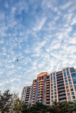 Airplane flying above the building Royalty Free Stock Image