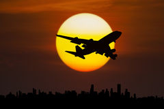 Airplane flying above city at dusk Royalty Free Stock Images