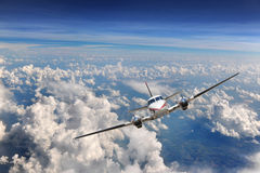 Airplane Flying above the clouds Stock Image
