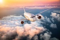 Airplane flying above clouds in dramatic sunset Stock Photography