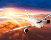 Airplane flying above clouds in dramatic sunset Stock Images