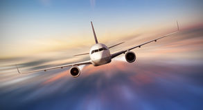 Airplane flying above clouds in dramatic sunset Royalty Free Stock Image