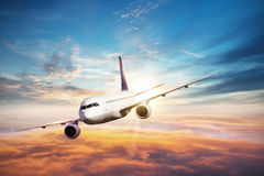 Airplane flying above clouds in dramatic sunset Stock Image