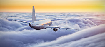 Airplane flying above clouds in dramatic sunset Royalty Free Stock Photos