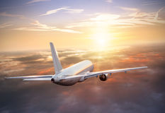 Airplane flying above clouds in dramatic sunset Stock Photos