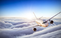 Airplane flying above clouds in dramatic sunset Royalty Free Stock Photo