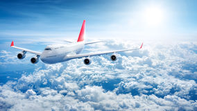 Airplane flying above clouds Stock Image