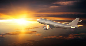 Airplane flying above clouds during sunset Royalty Free Stock Photos