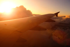 Airplane flying above clouds at sunset Stock Images