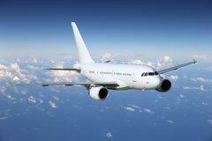 Airplane flying above the clouds stock photography