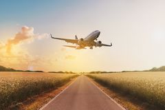 Airplane flying above empty road in rural landscape - travel co. Ncept royalty free stock image