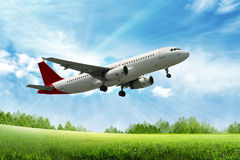 Airplane. Flying above green field Royalty Free Stock Image
