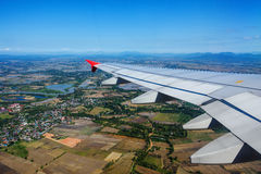 Airplane flying above green fields Stock Photo
