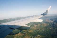 Airplane flying above green mountains Royalty Free Stock Images