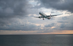 Airplane flying above the sea over cloudy sky. View from the beach on the landing airplane  above the sea over beautiful cloudy sky background Stock Photography
