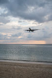 Airplane flying above the sea over cloudy sky. View from the sandy beach on the landing airplane  above the sea over beautiful cloudy sky background Stock Photography