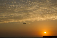 Airplane flying above sea at sunset Royalty Free Stock Image