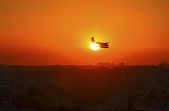 Airplane flying above tropical sea at sunset stock photography