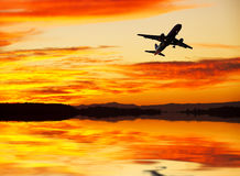 An airplane flying across the lake Stock Photos