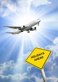Airplane flying against clouds and sunburst Stock Photos