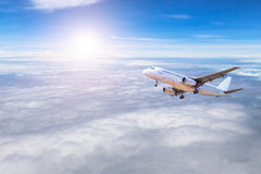Airplane flying away in to sky high altitude above the white clouds Royalty Free Stock Images