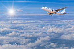 Airplane flying away in to sky high altitude above the white clouds Royalty Free Stock Photo