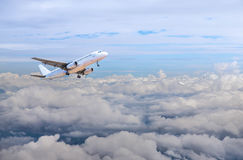 Airplane flying away in to sky high altitude above the white clouds Royalty Free Stock Photos