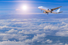 Airplane flying away in to sky high altitude above the white clouds with sunlight. Royalty Free Stock Photography