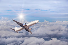 Airplane flying away in to sky high altitude above the white clouds with sunlight Royalty Free Stock Photos
