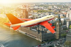 Airplane flying on a big city in the sunset Stock Photos