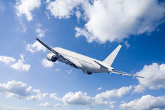 An airplane flying in the blue sky.  Stock Photos