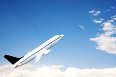 An airplane flying in the blue sky. Photo of airplane on the sky Royalty Free Stock Photos