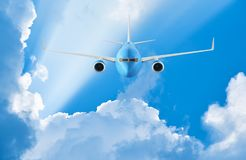 Airplane flying in the blue sky. Among clouds and sunlight Stock Photography