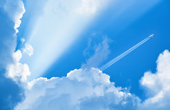 Airplane flying in the blue sky. Among clouds and sunlight Royalty Free Stock Photo
