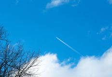 Airplane flying in the blue sky among clouds and sunlight royalty free stock photos