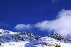 An airplane flying in the blue sky over the snow covered mountains in the alps switzerland.  Stock Images
