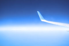 Airplane flying in a blue sky on a sunny day. View of airplane wing in a cloudless sky Royalty Free Stock Image