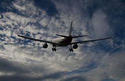 Airplane flying in blue sky with white clouds Royalty Free Stock Photography