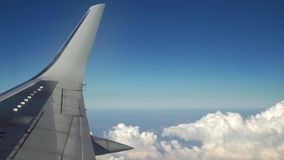 Airplane is flying in the blue sky through the white clouds. View of the airplane wing from the window. Traveling and stock footage